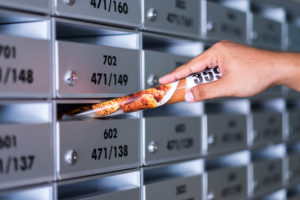 Close up man hand inserting ad paper into mailbox