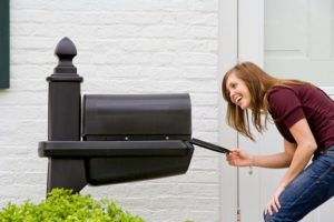 happy woman looking in the mailbox