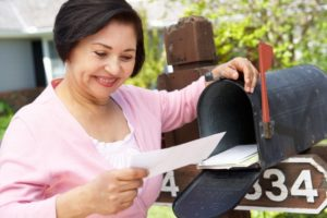 woman smiling while looking at a direct mailer